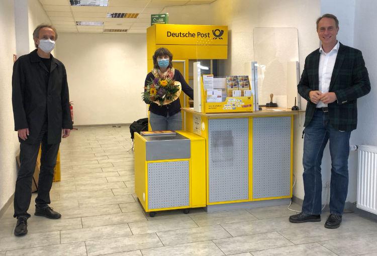 Stadtbürgermeister Falko Hönisch überreicht einer Mitarbeiterin zur Eröffnung der Postfiliale in St. Goar Blumen.